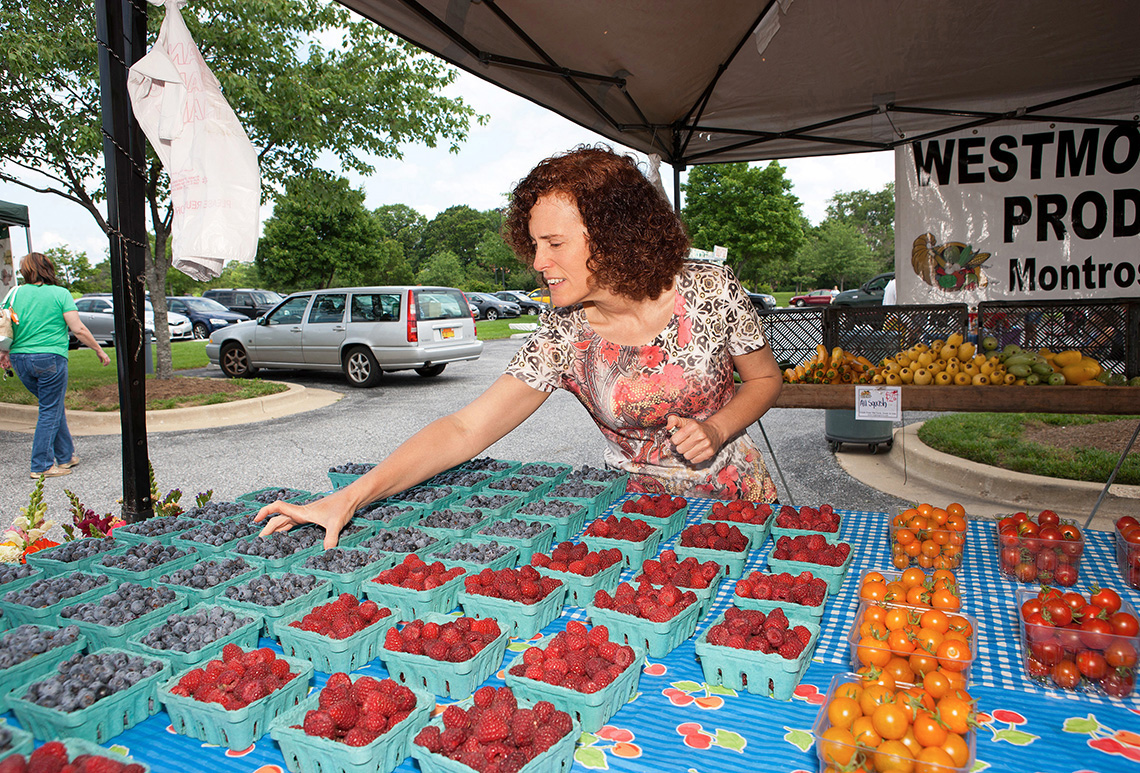 A woman selects a quart of blueberries at a farmers market