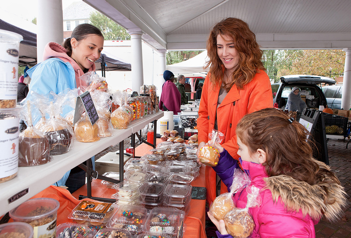 A mother and daughter select caramel apples from a vendor at a farmers market