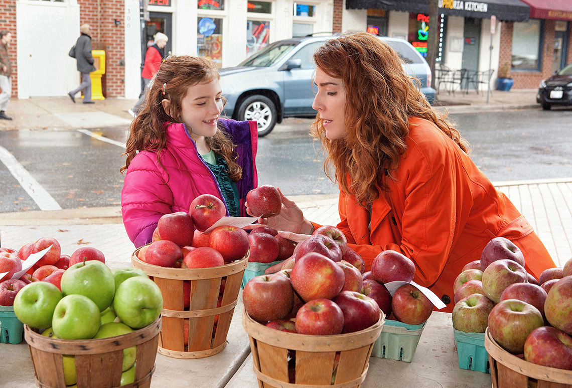 A mother and daughter look at apples at a farmers market