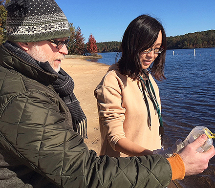 Two scientists look at a water sample collected at the Upper Oconee watershed