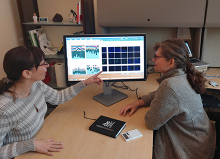ARS scientists review microscope images and data on a computer screen