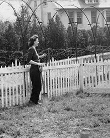 historical photo of two people talking over a fence