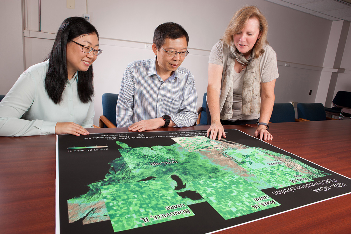 Three scientists looking at maps showing crop water use in U.S. agricultural landscapes