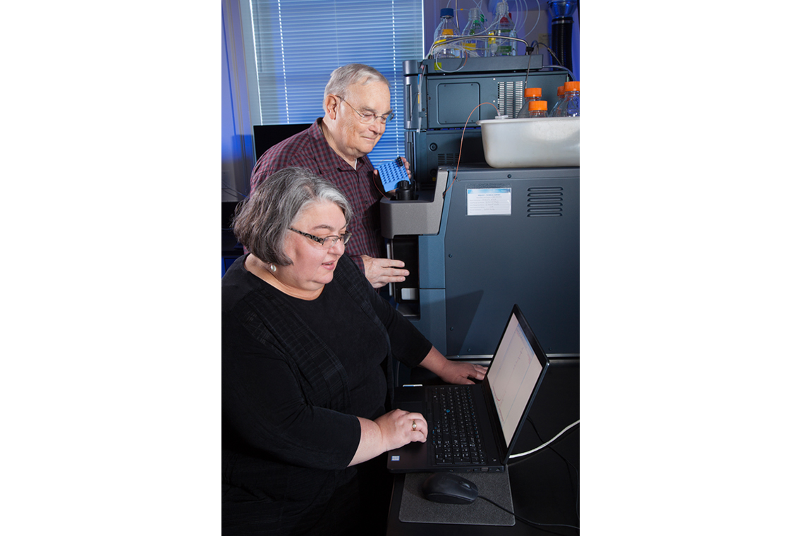 Two scientists using a mass spectrometer and looking at data on a screen