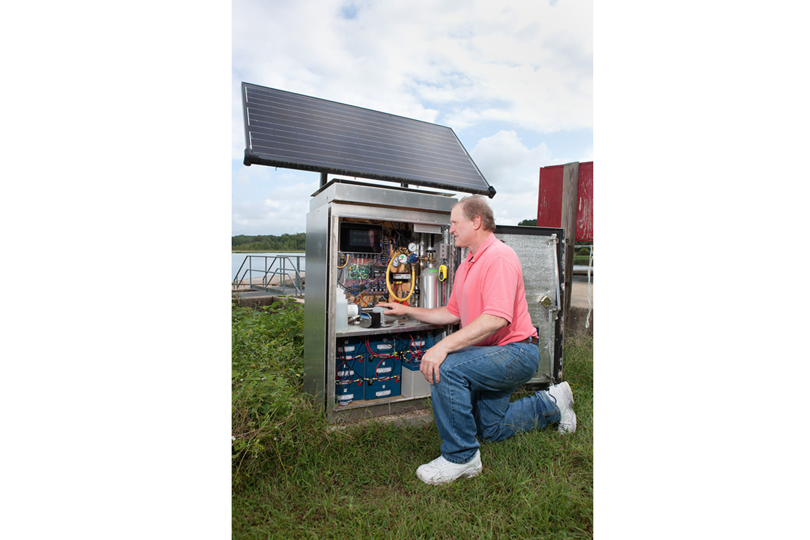 A scientist kneeling beside sensing equipment in a field