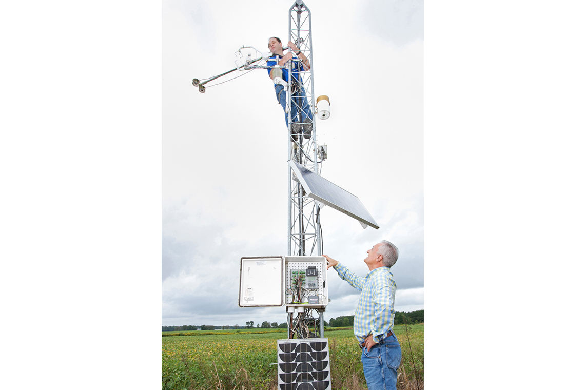 Two scientists working with a meteorological tower in a field