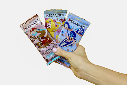 A hand holding three packaged ReGrained bars.
