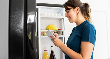 Woman standing in front of an open refrigerator while making a list.